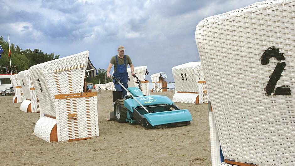 Walk-behind beach cleaner BeachTech Sweepy on the beach with beach chairs