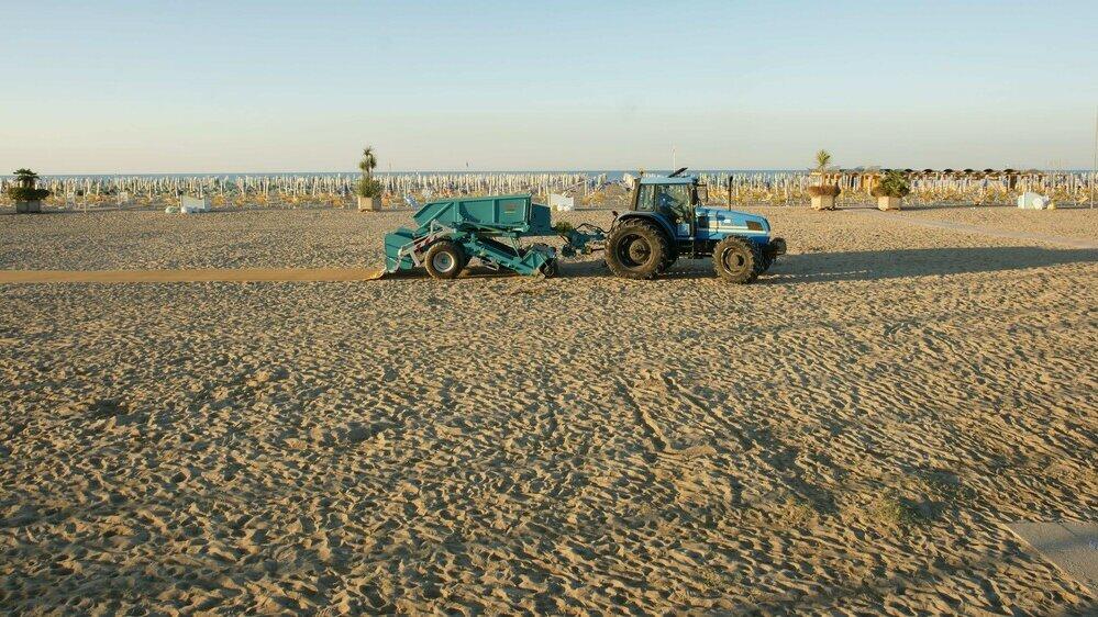 Gezogener Strandreiniger mit Traktor am Strand